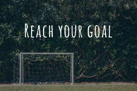 Soccer goal at the outdoor amateur field surrounded by green plant wall. Reach you goal wording. Close to nature, healthy space, team game, goal reaching concept