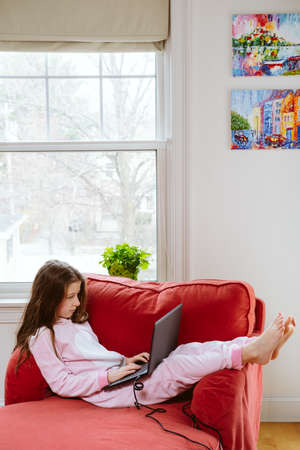 Preteen girl enjoyes homeschooling in comfy pijama and cozy sofa chair. Remote education, virus protection, social distancing and lockdown concept. Vertical option with place for text