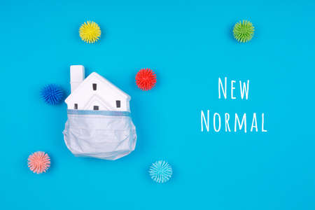 Cute little house covered with medicine mask and plastic balls as viruses on blue with New Normal wording. Coronavirus pandemic reduction, moving to new normal, economy reopening concept