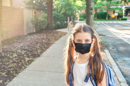 Elementary school student in a cloth dust mask with backpack in the street. Preteen girl is going to school in new normal. Education, coronavirus, back to school concept