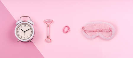 Pink drop with cute fluffy sleep mask, jade roller, watch and pink accessories. Sleep management and optimization, beauty sleep, beauty and sleep log concept. Place for text, banner format