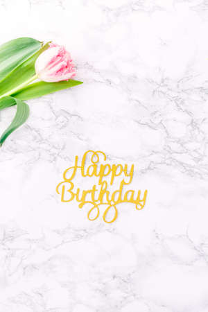 Pink tulips and gold Happy birthday letters on white marble background. Spring and celebration concept. Copy space Top view.. Vertical Standard-Bild