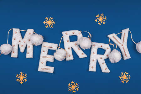 White and golden knitted garland with word MERRY and white pompons on classic blue decorated with golden snowflakes. Holiday celebration concept, Christmas card