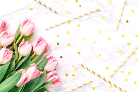 Pink tulips and gold festive straws on white marble background. Spring and celebration concept. Copy space Top view. Horizontal Standard-Bild