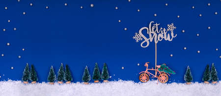 Funny cozy scene with Christmas toys on classic blue. Christmas tree is moved home by bicycle on the snow road with stars shining and Let Snow wording. Horizontal banner format with place for text Standard-Bild