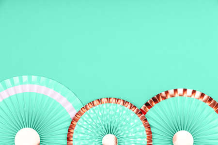 Turquoise green and golden paper fans on monochrome drop. Party, decorations, celebration backdrop with place for text