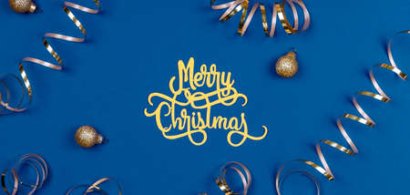 Holiday background with Merry Christmas wording, golden balls, and ribbons on classic blue. Holiday celebration card concept in banner format