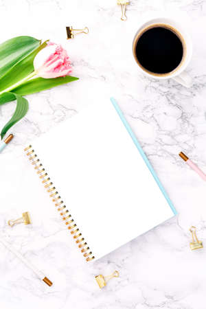 Pink tulips with festive stationary and coffee on white marble background. Online and remote work and learning, home office and career concept. Copy space. Top view.. Vertical Standard-Bild