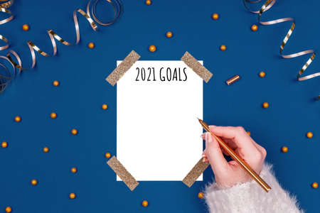 Woman writes New Year Resolutions. Flat lay image in gold and classic blue colors with isolated white card. Horizontal