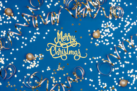 Holiday background with Merry Christmas wording, golden confetti, balls and ribbons on classic blue. Holiday celebration card concept Standard-Bild