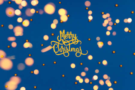 Pattern with golden Merry Christmas wording and holiday round sprinkles on classic blue with festive warm bokeh. Festive holiday drop with place for text
