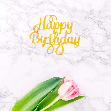 Pink tulips and gold Happy birthday letters on white marble background. Spring and celebration concept. Copy space Top view.. Square