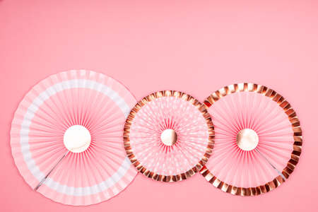 Pink and golden paper fans on pink drop. Party, decorations, celebration backdrop with place for text
