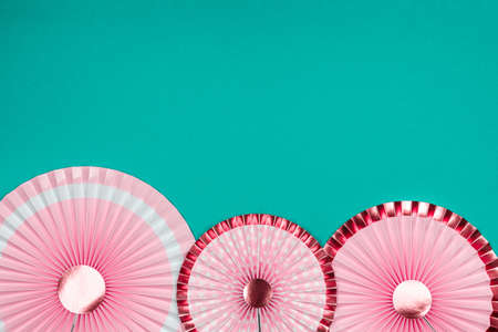 Pink and golden paper fans on turquoise drop. Party, decorations, celebration backdrop with place for text Standard-Bild