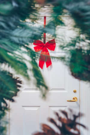 White appartment door with seasonal greens out of focus and red bow. Holiday decorations concept Standard-Bild