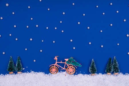 Funny cozy scene with Christmas toys on classic blue. Christmas tree is moved home by bicycle on the snow road with stars shining. Horizontal