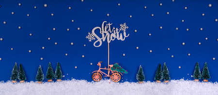 Funny cozy scene with Christmas toys on classic blue. Christmas tree is moved home by bicycle on the snow road with stars shining and Let Snow wording. Horizontal banner format Standard-Bild
