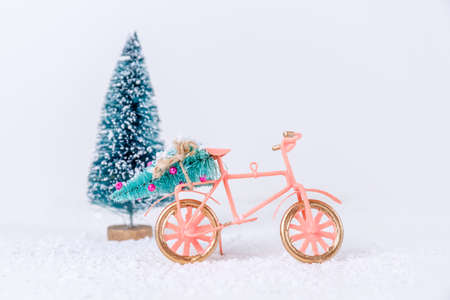 Bicycle with Christmas tree in the snow on white background. Holiday season, Christmas, Holiday celebration card concept