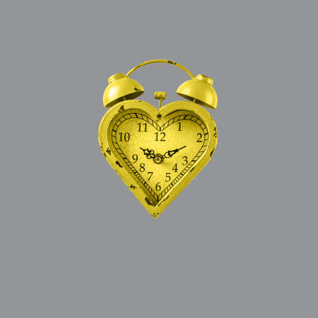 Heart shaped yellow clock on gray background. Valentines day and love infitity and duration concept. Square Standard-Bild