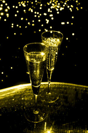 Two glasses of champagne on the glass table on black background, toned in yellow