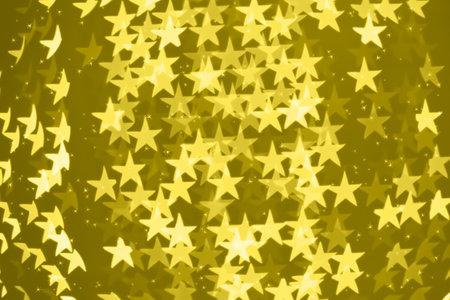 Star shaped holiday blurred bokeh illuminating yellow background. Christmas background with sparkles. Celebration background. Horizontal