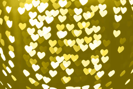 Heart shaped holiday blurred yellow bokeh background. Christmas background with sparkles. Celebration background. Horizontal Standard-Bild