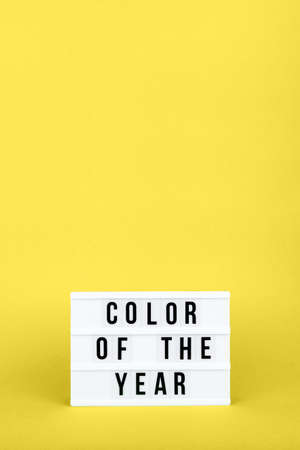 Retro lightbox with Color of the year wording on the trendy solid yellow backdrop in vertical format, place for text