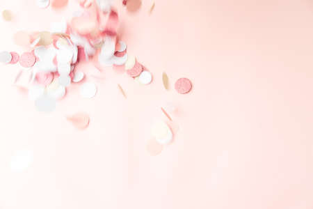 Multicolor pink, gold and white confetti falling on the pastel light pink background, holiday celebration backdrop with place for text Standard-Bild