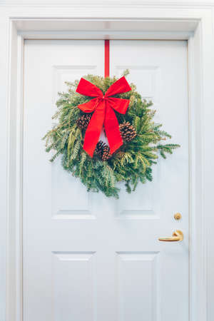 White appartment door with seasonal greens and red bow. Holiday decorations concept Standard-Bild
