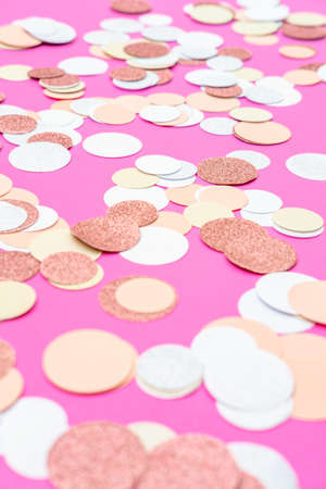 Multicolor pink, gold and white confetti on the bright pink background, holiday celebration backdrop, place for text