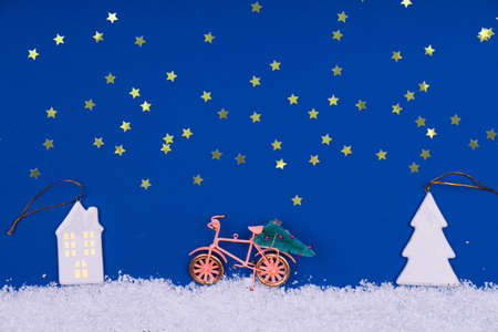 Funny cozy scene with Christmas toys on classic blue. Christmas tree is moved home by bicycle on the snow road with stars shining. Horizontal Standard-Bild - 160518209