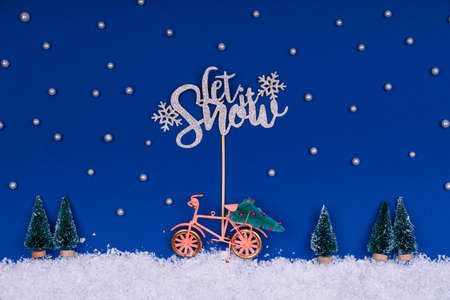 Funny cozy scene with Christmas toys on classic blue. Christmas tree is moved home by bicycle on the snow road with stars shining and Let Snow wording. Horizontal Standard-Bild - 160518219