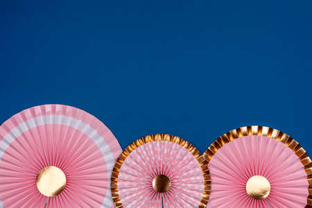 Pink and golden paper fans on classic blue drop. Party, decorations, celebration backdrop with place for text