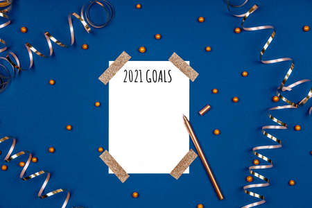 Isolated white card with 2021 goals wording and golden pen with festive ribbons and confetti. Flat lay background in gold and classic blue colors for any celebration and party occasion. Horizontal
