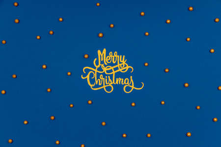 Pattern with golden Merry Christmas wording and holiday round sprinkles on classic blue. Festive holiday drop with place for text