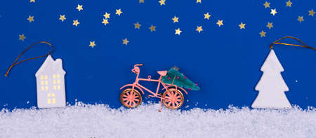 Funny cozy scene with Christmas toys on classic blue. Christmas tree is moved home by bicycle on the snow road with stars shining. Horizontal banner format Standard-Bild - 160629549