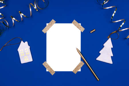 Isolated white card mock up with festive golden ribbons and Christmas toys. Flat lay background in gold and classic blue colors for any celebration and party occasion. Horizontal
