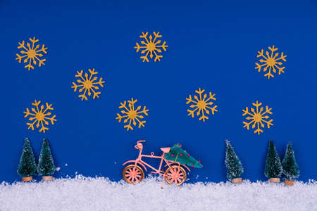 Funny cozy scene with Christmas toys on classic blue. Christmas tree is moved home by bicycle on the snow road with big golden snowflakes. Horizontal Standard-Bild - 160682791