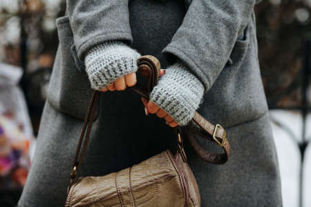 A girl in a coat and knitted gloves is holding a leather bag. Close-up of hands. A woman expects, nervous. Compressed hands, beautiful manicure