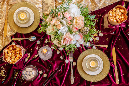 Decorated dinning table elegance setting with romantic flowers, burning candles and gold crockery. View from above Stock Photo