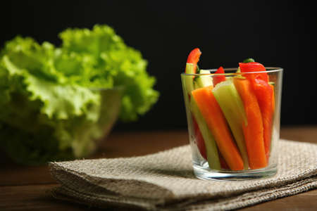 Pepper, carrots, celery, raw cucumber are cut into strips. In a glass beaker. Next to it are lettuce leaves, basil. On a background of cloth, burlap, wooden table, black background.