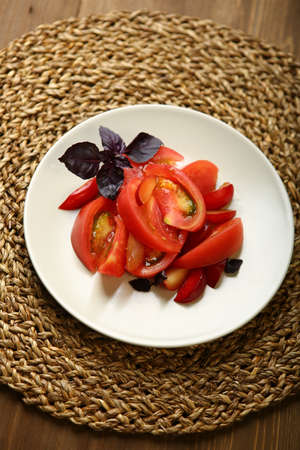Salad of tomato and red plums with basil for a healthy diet. Low-calorie food for body weight control. Fast snack. On a wooden table, a wicker stand. Close-up, upper angle Фото со стока