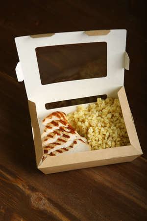 Grilled chicken with slices, with bulgur in a paper container. Delivery at home, a quick snack. Low-calorie, dietary food for a healthy lifestyle.