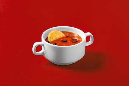 Solyanka with olives, olives and lemon on a monophonic red background in a deep white plate with handles. Side view