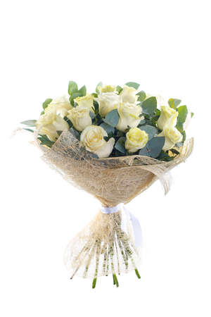 Bouquet of white roses, eucalyptus and Ruscus in a package with a white ribbon. A holiday, a gift for a woman. Big and smart. Side view. Isolated.