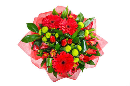 Bouquet of gerberas, tulips, bush chrysanthemums, Ruscus, alstroemeria, aspidistra. In red packing. A holiday, a gift for a woman. Big and smart. View from above Isolated