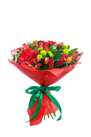 Bouquet of gerberas, tulips, bush chrysanthemums, Ruscus, alstroemeria, aspidistra. In red packing with green ribbon. A holiday, a gift for a woman. Big and smart. Side view. Isolated