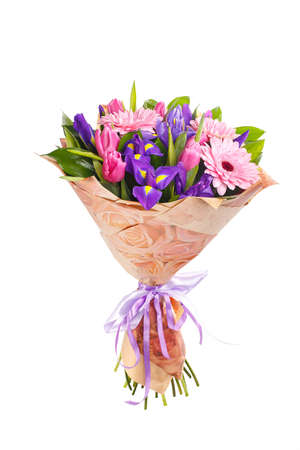 Bouquet of pink gerberas, violet irises and pink, crimson tulips in a package of paper and satin, lilac ribbon. A holiday, a gift for a woman. Big and smart. Side view. Isolated.