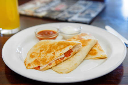 Quesadilla with chicken and tomatoes, two sauces from tomatoes and sour cream. Low key. Side view.