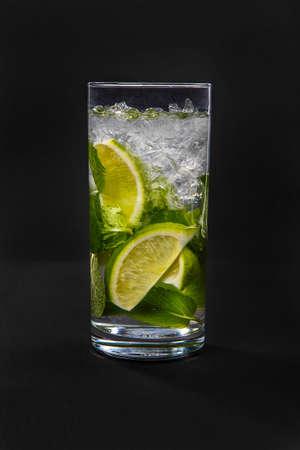 Summer drink with lime and mint, ice on isolated black background. Direct perspective, cool, refreshing